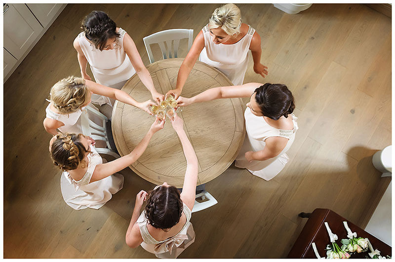 Bridesmaids raise a glass over round table prior to leaving for ceremony Chrishall Cambridgeshire Village Wedding