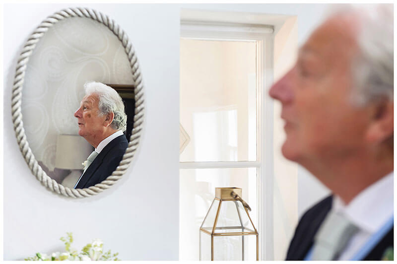 Father of bride reflected in mirror watches bride come down stairs first look