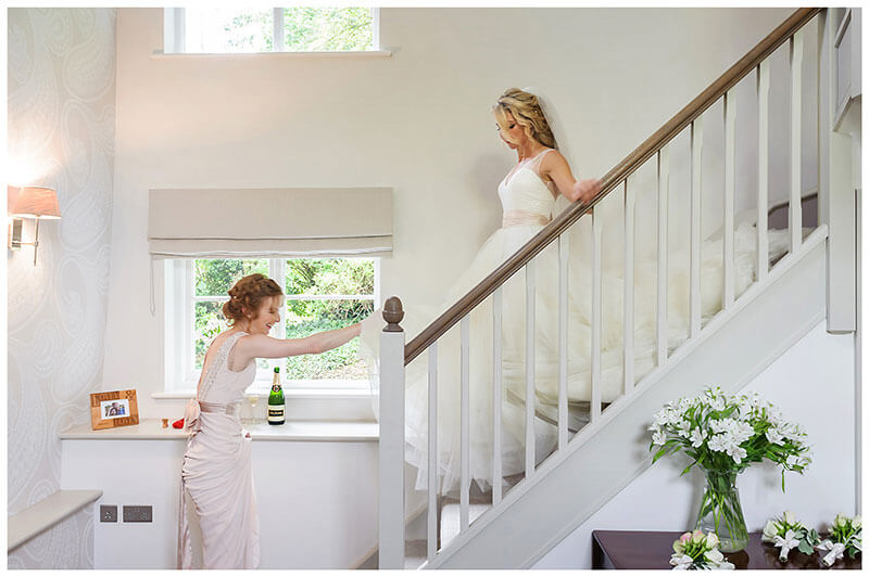 Bride comes down stairs in dress assited by bridesmaid