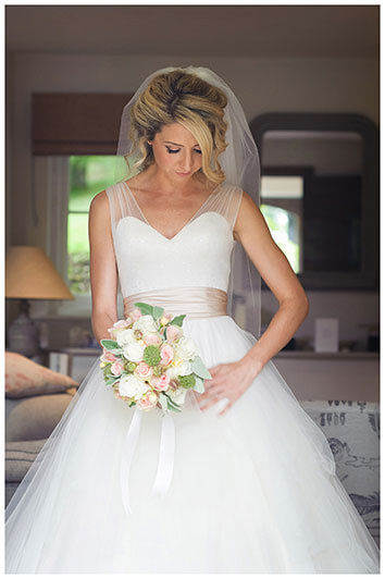 Bride brushes dress with her hand while holding bouquet