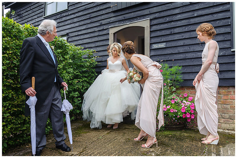 Father of bride watches as she leaves for church assisted by bridesmaids