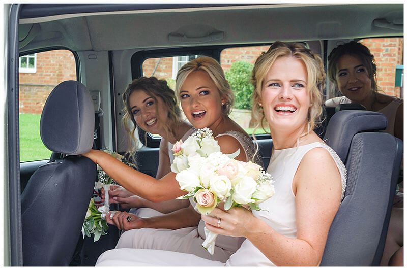 Bridesmaids smiling sat in transport waiting to go to the church