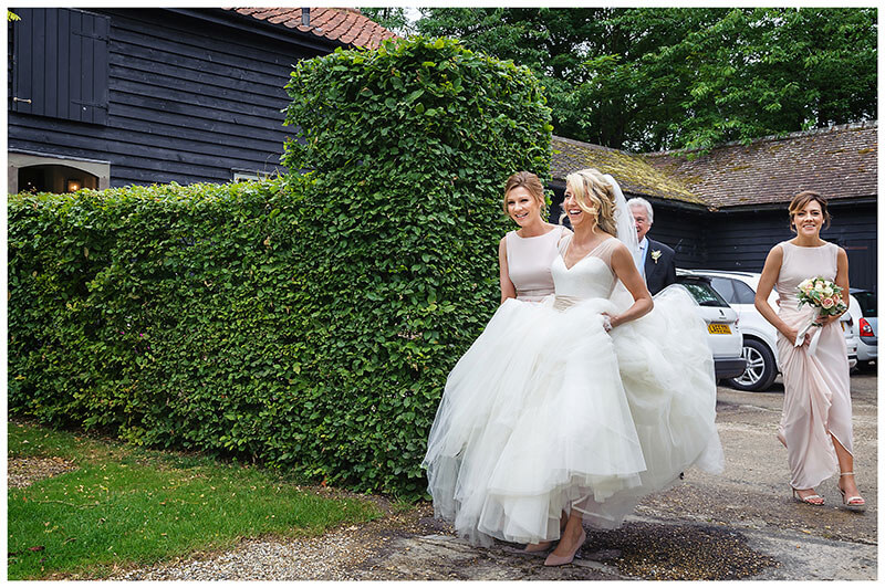 laughing bride lifting dress off ground helped by bridesmaid as she leaves for church Chrishall Cambridgeshire Village Wedding