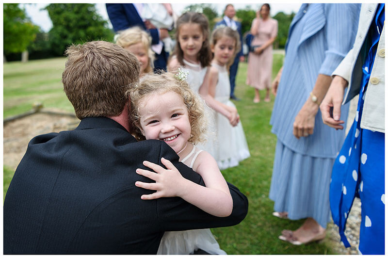 smiling Flower girl hugs groom before Chrishall Cambridgeshire Village Wedding