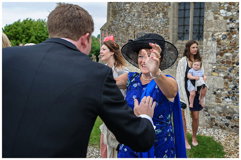 female guest in blue goes to give groom a hug with smile on her face outside Chrishall Cambridgeshire Village Wedding