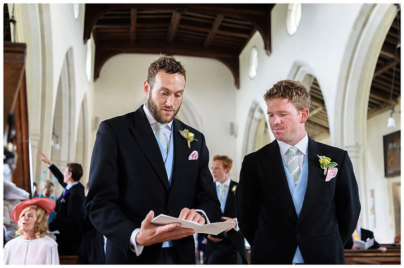 Groom and usher at alter looking at order of service