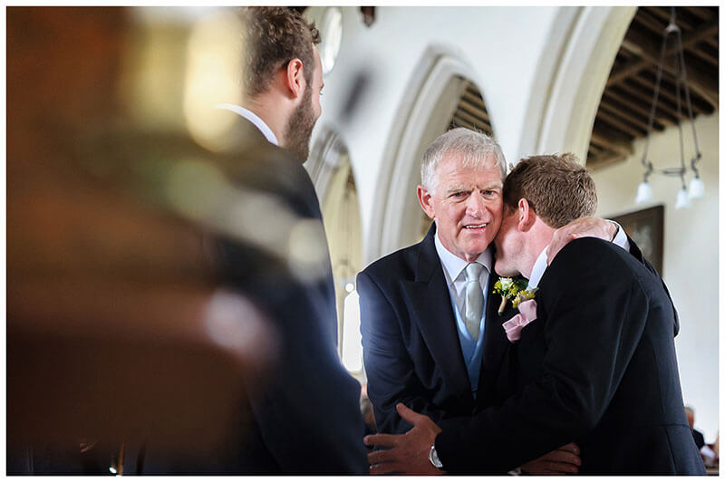 Groom gets a hug from father as he stands at alter waiting for bride at Chrishall Church in Cambridgeshire Village Wedding
