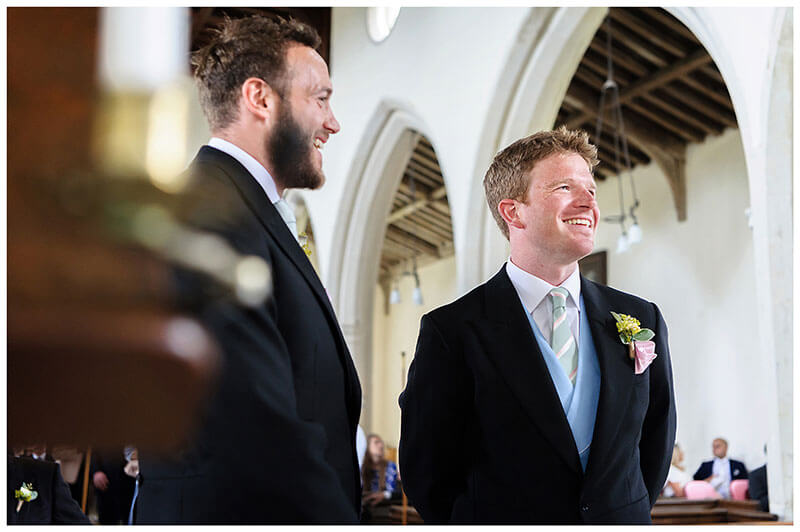groom and best man laugh while stood at alter waiting for bride during Chrishall Church Cambridgeshire Village Wedding