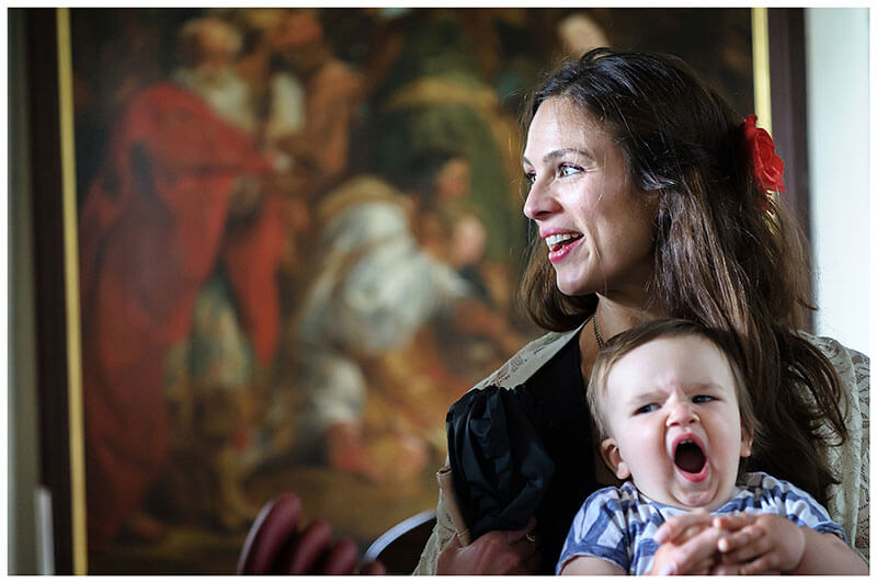 Mother smiles standing in front of large painting while baby yawns in side Chrishall village Church