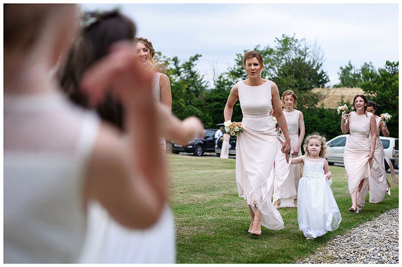Flowergirls welcoming bridesmaids at church Chrishall in Cambridgeshire
