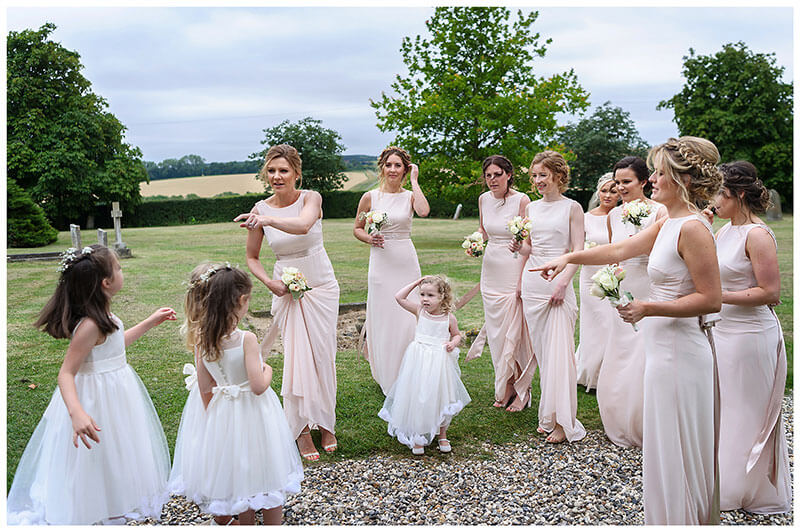 Bridesmaids and flowergirls pointing out who goes first Chrishall Cambridgeshire Village Wedding