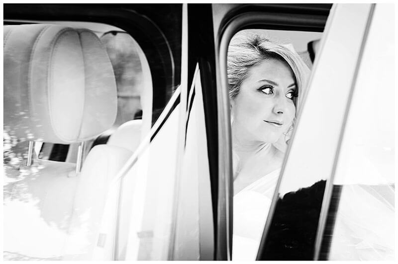 Bride glances over shoulder as she sits in car