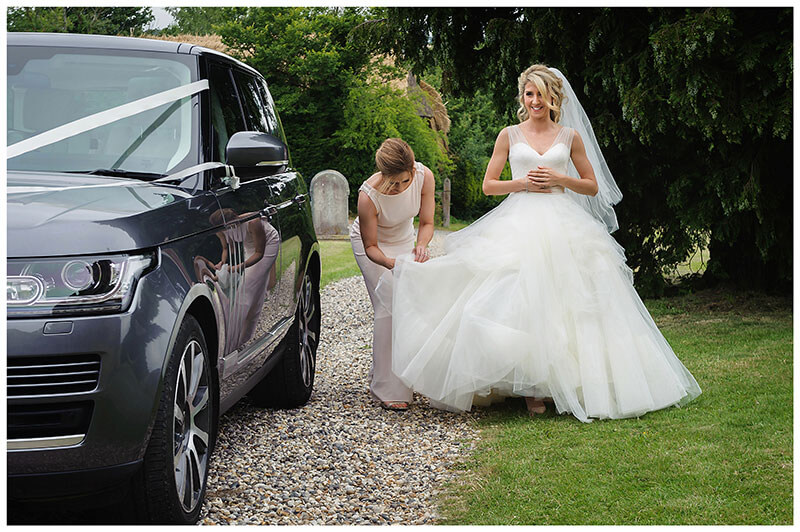 Bridesmaid adjusts brides dress after she gets out of car