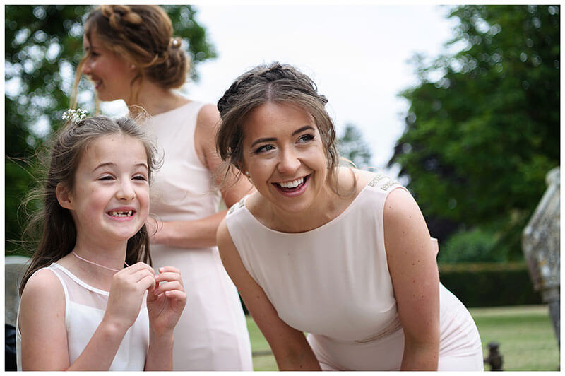 smiling Bridesmaid and flowergirl watch the arrival of the bride
