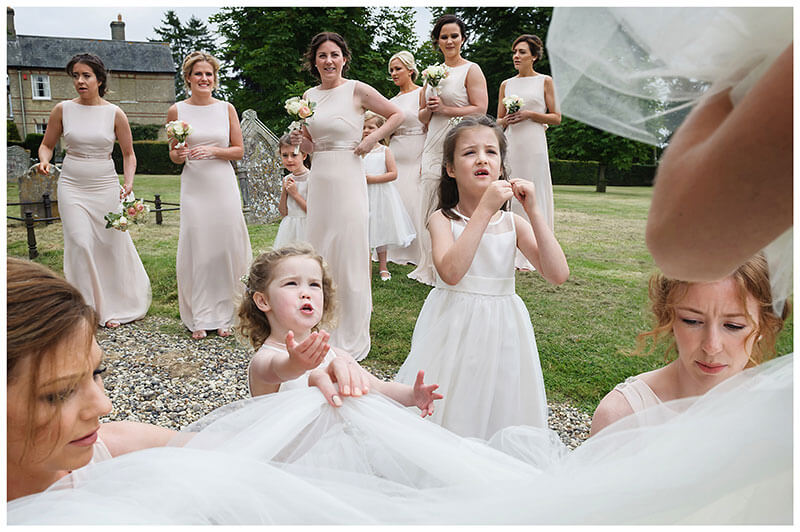 Flowergirls talking to bride as bridesmaids adjust dress watched by remaining bridesmaids