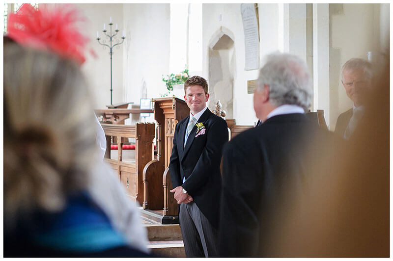 Groom watches bride approach down aisle during Chrishall Church ceremony