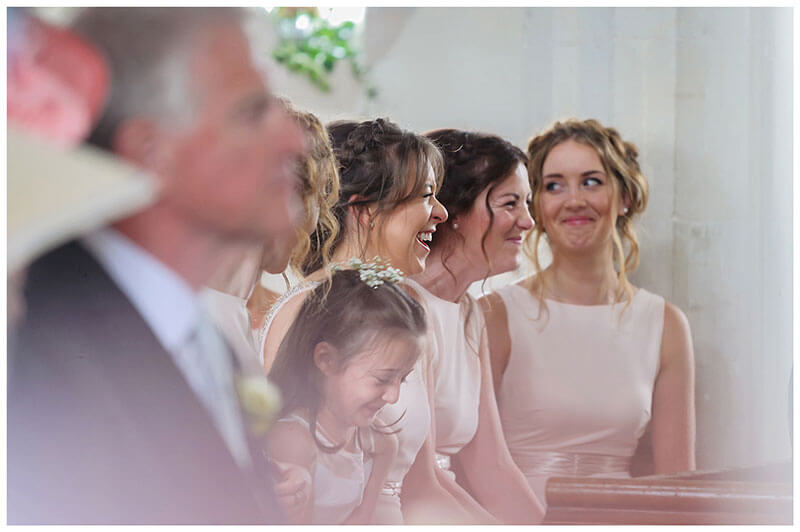 gigling bridesmaids during church wedding ceremony