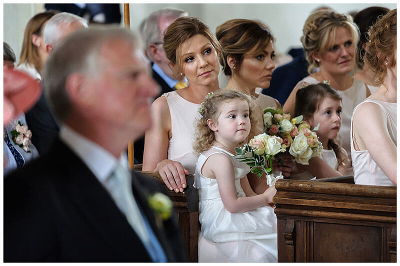 Bridesmaid and flower girls sat in church at Chrishall Cambridgeshire Village Church Wedding