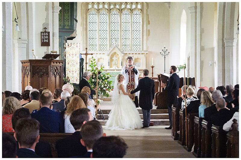 Bride looks over shoulder during ceremony at Chrishall Church Wedding