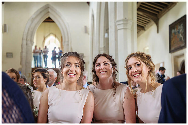 Smiling bridesmaids during ceremony at Chrishall Village Church Wedding