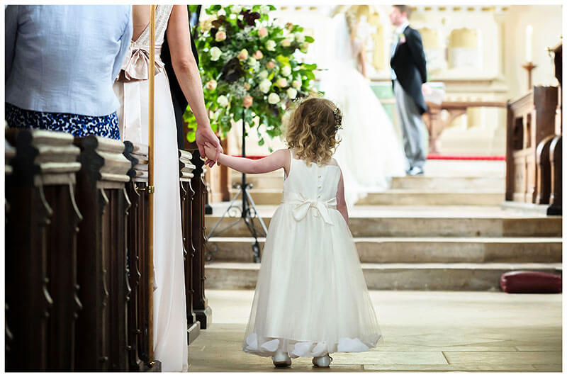 Flower girl holding mothers hand standing in aisle watches proceedings during ceremony Chrishall Church Cambridgeshire Wedding