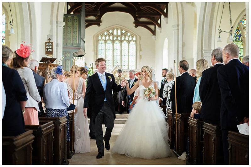 Smiling bride groom hold hands as they walk down aisle after ceremony at Chrishall Church