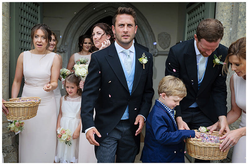 Little boy takes some confetti as usher and bridesmaids come out of Chrishall church