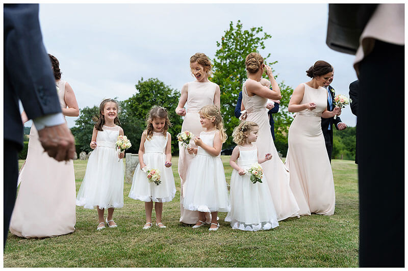 Bridesmaids and flowergirls lined up to throw confetti