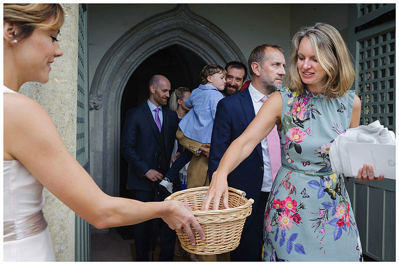 female guest takes confetti from wicker basket held by bridesmaid at exit to church in Chrishall village