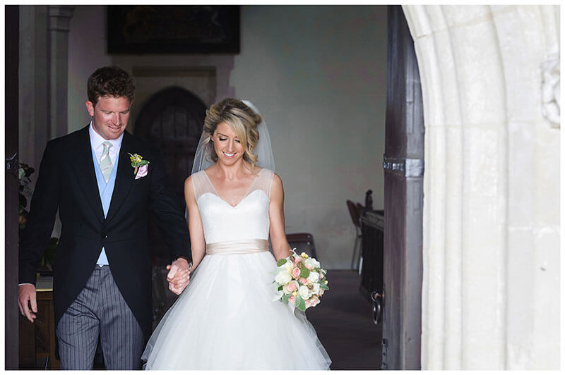 Bride groom come out of church smiling after Chrishall Cambridgeshire Village Church Wedding