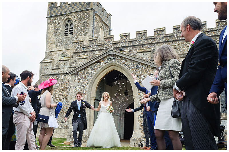 bride groom come out of church as guest start to throw confetti outside church after ceremony Wedding