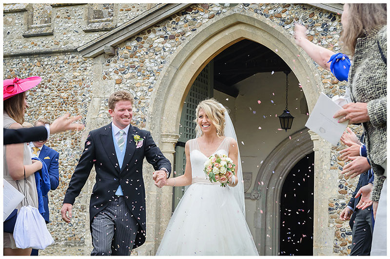 Smiling bride groom hold hands as guest throw confetti church door way in background