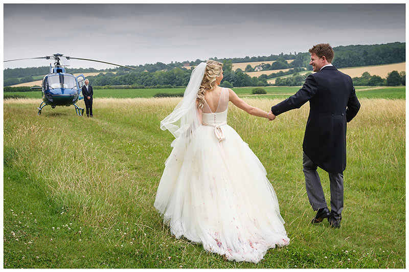Bride groom look at each other holding hands as they walk towards helicopter after church Village Wedding