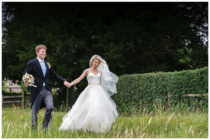 Bride groom smiling walking hand in hand groom holding brides bouquet in long grass
