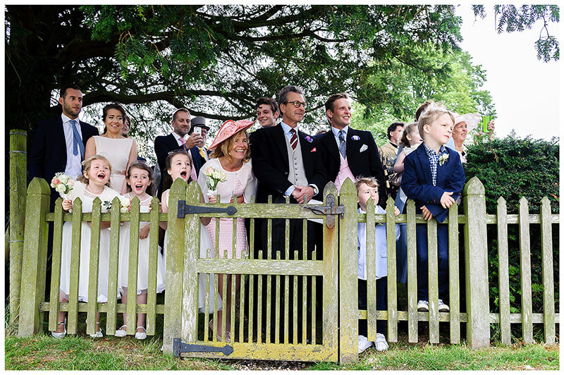 Guests standing behind fence looking towrds helicopter with bride groom waiting for it to take off