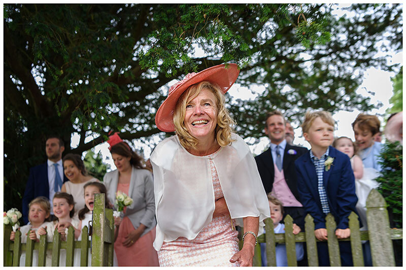 Grooms mother looking excited at helicopter taking off Cambridgeshire Village Wedding