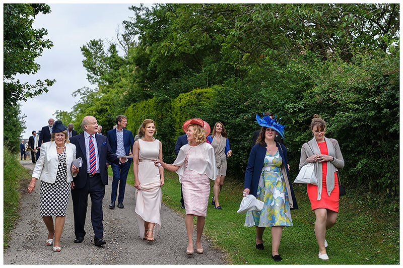 Wedding guests walking to reception after ceremony during Chrishall Cambridgeshire Village Wedding