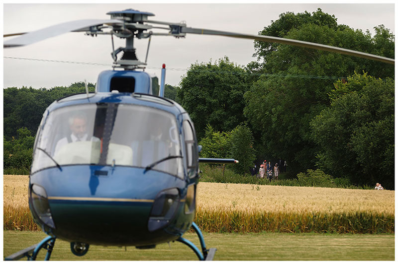Wedding guests in background walking to reception with helicopter in foreground Chrishall Cambridgeshire Village Wedding