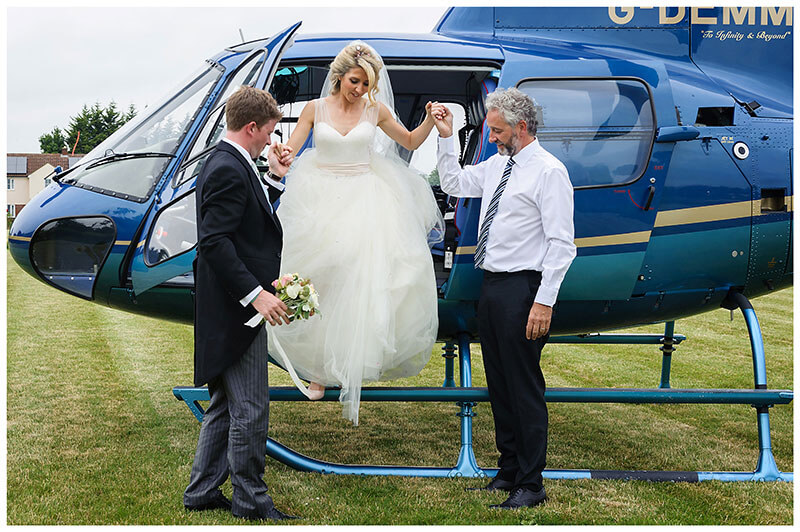Bride helped out of helicopter by pilot and groom at Chrishall Cambridgeshire Village Wedding