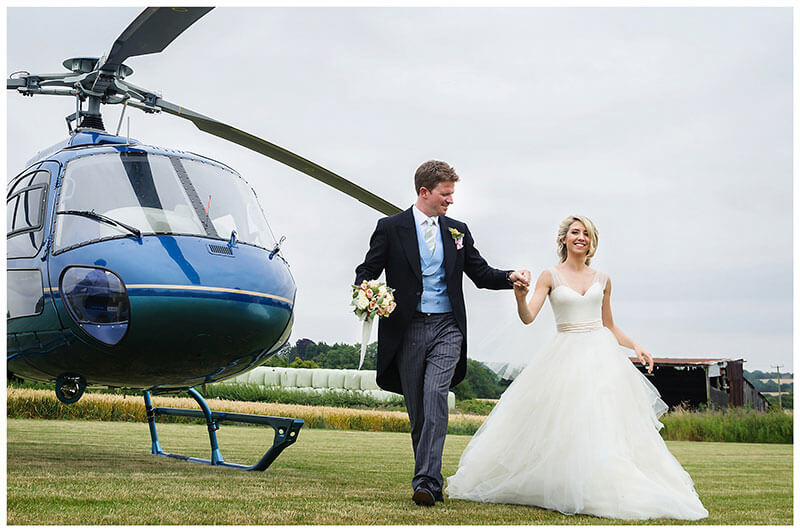 Bride & groom walking in front of helicopter groom holding brides bouquet Chrishall Cambridgeshire Village Wedding