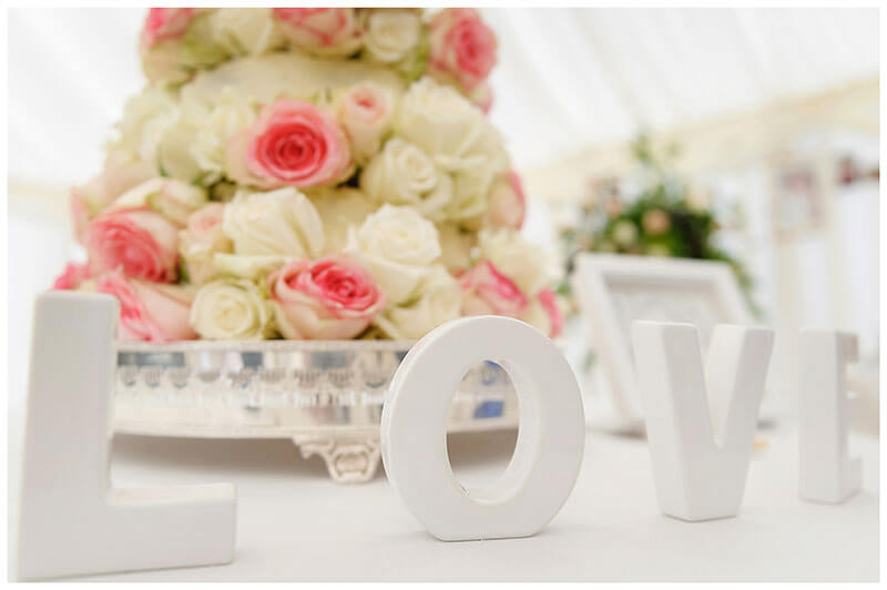 White LOVE letters in front of wedding cake