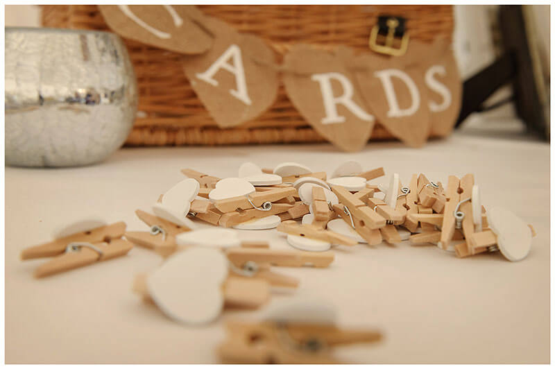 cloths pegs on table with hearts attached in front of cards here basket