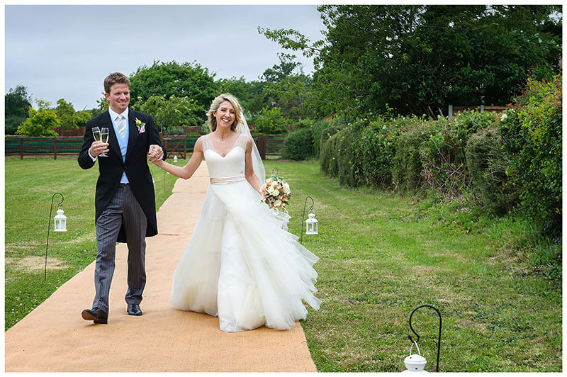 Smiling bride and groom holding hands walking along hessian carpet arrive at reception