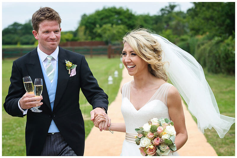 Smiling bride holding grooms hand as they arrives at reception