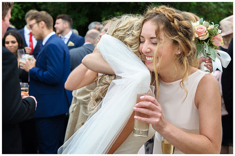 Bridesmaid closes eyes as she gives bride a big hug