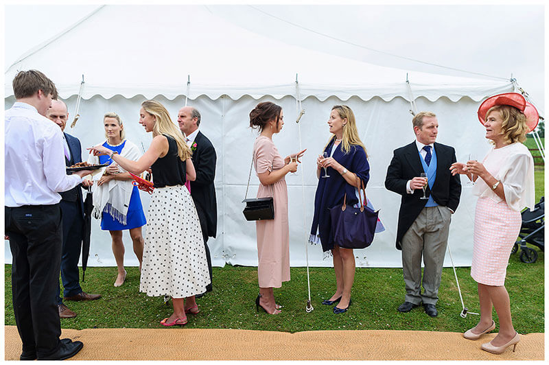 wedding guests standing next to marquee talking