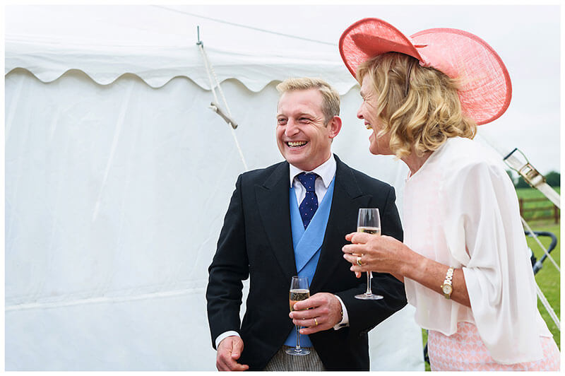 man and lady in pink hat laughing outside marquee Village Wedding