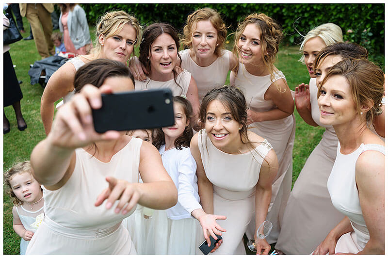 Bridesmaids and flower girls selfie during reception