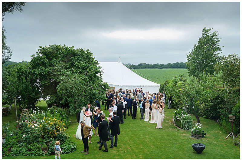 Marquee in garden guests on lawn during Cambridgeshire Village Wedding