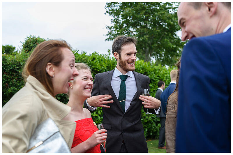 laughter from other guests as Man touches his nipples through his suit during wedding reception